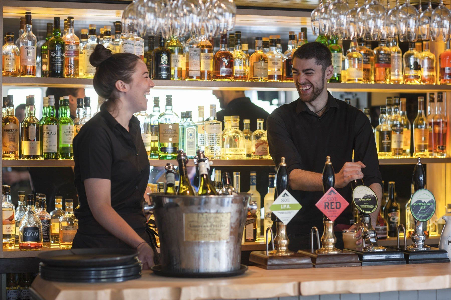 Staff behind the bar at Kylesku Hotel, Sutherland